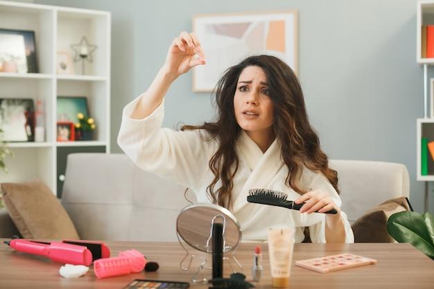 Jovem mulher segurando o pente sentado à mesa com ferramentas de maquiagem na sala de estar
