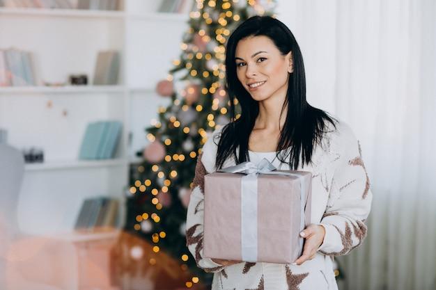 Jovem mulher segurando o presente de natal pela árvore de natal