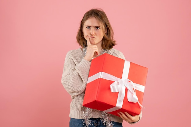 Jovem mulher segurando o presente de natal pensando de frente