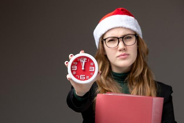 Jovem mulher segurando o relógio de frente com arquivos no livro da faculdade de aula de parede escura