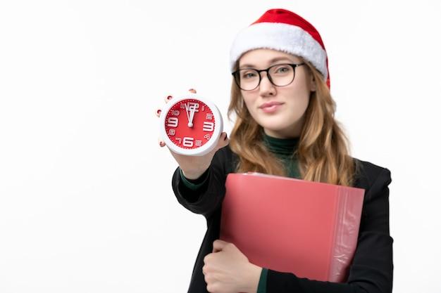 Jovem mulher segurando o relógio de frente com arquivos no livro de parede branca.