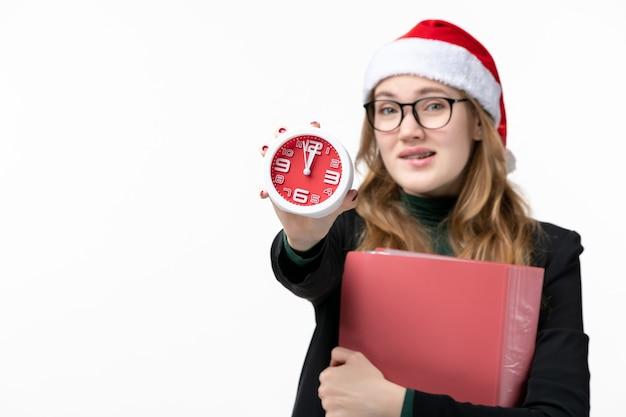 Jovem mulher segurando o relógio de frente com arquivos nos livros da faculdade de parede branca