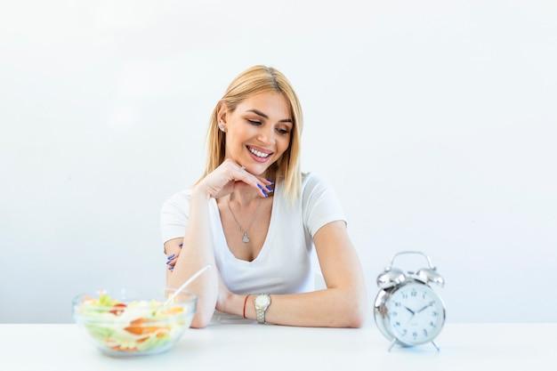 Jovem mulher segurando o relógio e comida saudável de salada conceito de jejum intermitente. tempo para perder peso, controle de alimentação ou tempo para o conceito de dieta.