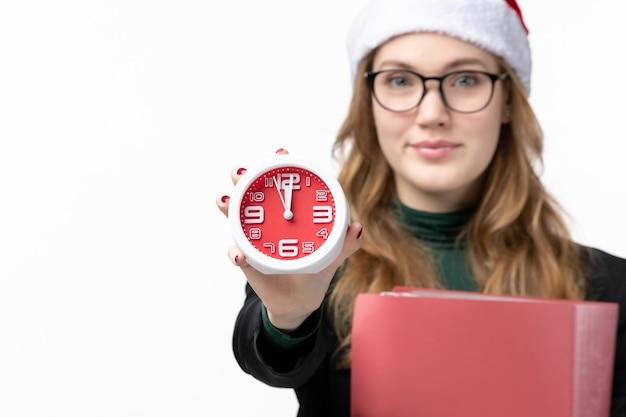 Jovem mulher segurando o relógio e os arquivos nos livros da faculdade de parede branca