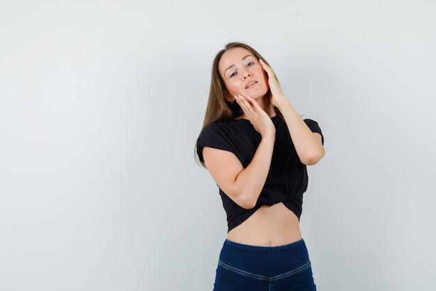 Jovem mulher segurando o rosto com as mãos na blusa preta e parecendo atraente