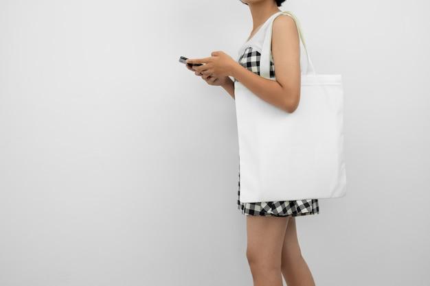 Jovem mulher segurando o saco de algodão eco e usando móvel isolado no branco