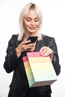 Jovem mulher segurando o saco de presente colorido ao tirar uma foto na parede branca.