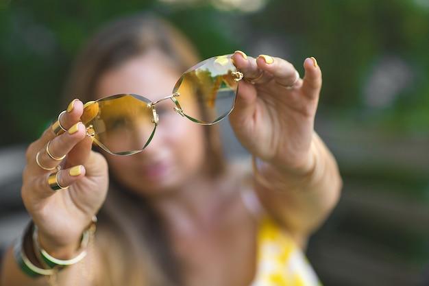 Jovem mulher segurando óculos de sol amarelos nas mãos na frente da câmera. ainda de acessórios elegantes