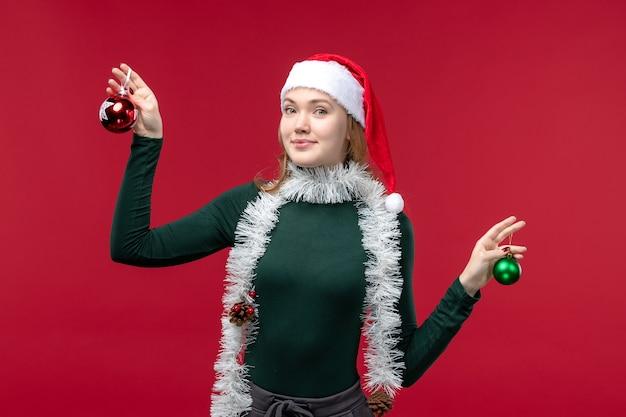 Jovem mulher segurando os brinquedos da árvore de natal no fundo vermelho.