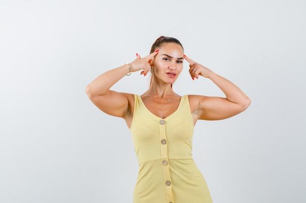 Jovem mulher segurando os dedos nas têmporas com vestido amarelo e parecendo inteligente. vista frontal.