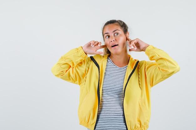 Jovem mulher segurando os dedos perto das orelhas em t-shirt, jaqueta e parecendo um sonho, vista frontal.