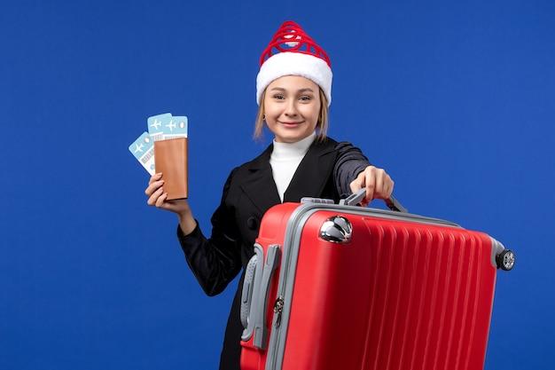 Jovem mulher segurando os ingressos com a bolsa no avião de fundo azul, férias, vista frontal