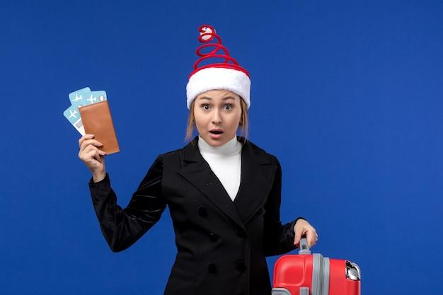 Jovem mulher segurando os ingressos com a bolsa no fundo azul de férias em avião