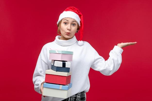 Jovem mulher segurando os presentes de ano novo de frente em um fundo vermelho