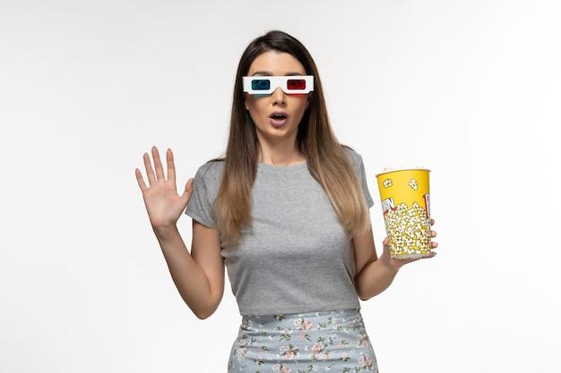 Jovem mulher segurando pipoca e assistindo filme com óculos de sol na mesa branca.