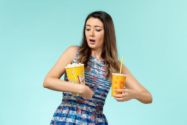 Jovem mulher segurando pipoca e bebida na mesa azul de frente