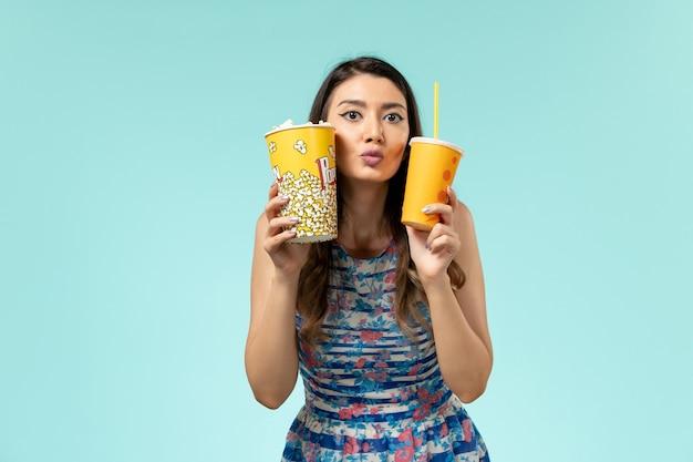 Jovem mulher segurando pipoca e bebida na superfície azul de frente