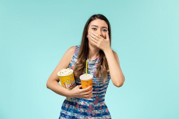 Jovem mulher segurando pipoca e bebida, rindo na superfície azul de frente
