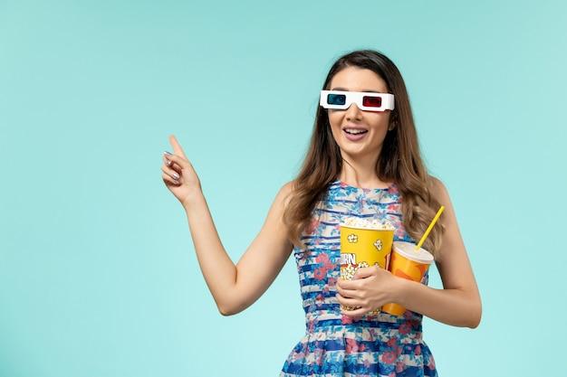 Jovem mulher segurando pipoca em óculos de sol d na superfície azul de vista frontal