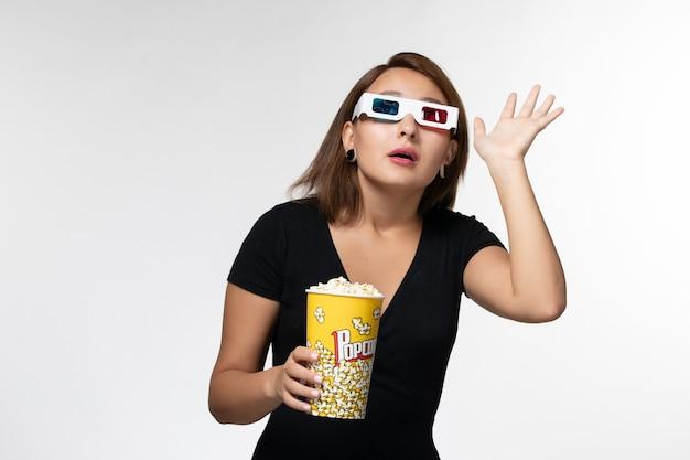 Jovem mulher segurando pipoca em óculos de sol de vista frontal assistindo filme na superfície branca