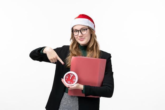 Jovem mulher segurando relógio e arquivos na mesa branca livro aula faculdade