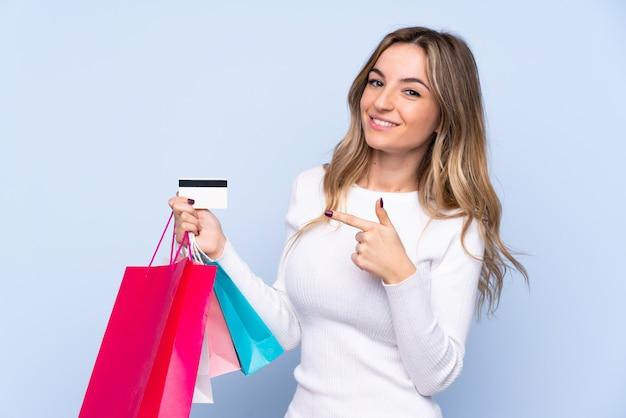Jovem mulher segurando sacolas de compras e cartão de crédito
