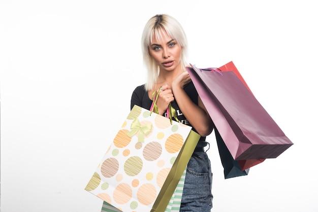 Jovem mulher segurando sacolas de compras na parede branca com expressão chocada.