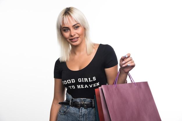 Jovem mulher segurando sacolas de compras na parede branca.