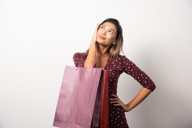 Jovem mulher segurando sacolas na parede branca.