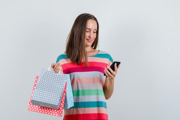 Jovem mulher segurando sacos de papel e olhando para o telefone em vista frontal da camiseta.