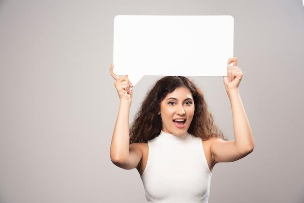Jovem mulher segurando sobrecarga de cartaz de discurso branco em branco vazio. foto de alta qualidade