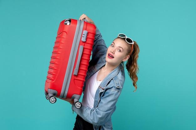 Jovem mulher segurando sua bolsa vermelha e se preparando para a viagem na mesa azul