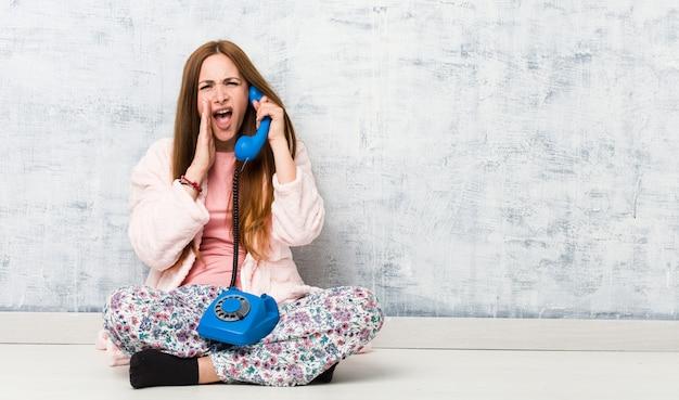 Jovem mulher segurando telefone fixo gritando animado para a frente