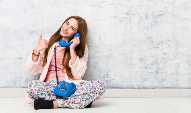 Jovem mulher segurando telefone fixo sorrindo e levantando o polegar