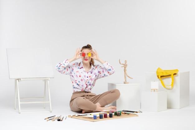 Jovem mulher segurando tintas coloridas dentro de latas em fundo branco.