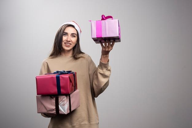 Jovem mulher segurando três caixas de presentes de natal.