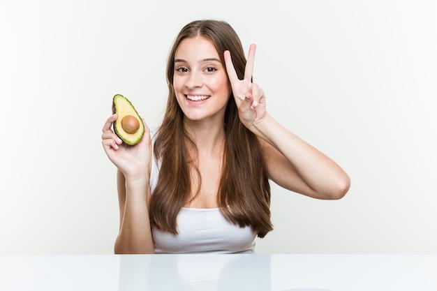 Jovem mulher segurando um abacate mostrando sinal de vitória e sorrindo amplamente