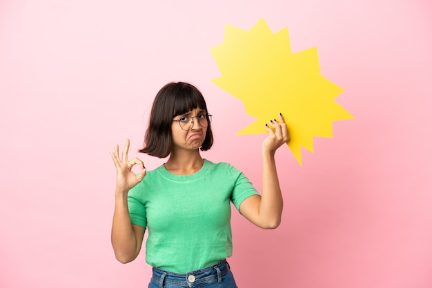 Jovem mulher segurando um balão de fala vazio e fazendo sinal de ok