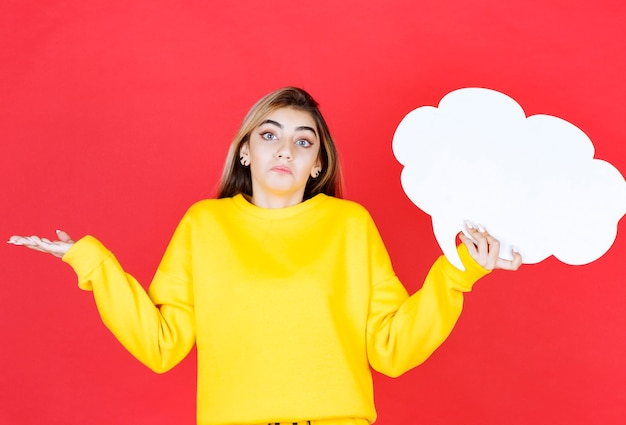 Jovem mulher segurando um balão de fala vermelho