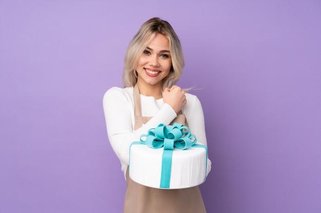 Jovem mulher segurando um bolo sobre parede isolada