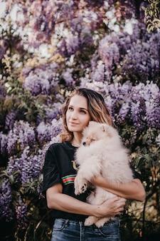 Jovem mulher segurando um cachorrinho da pomerânia em um fundo de flores de lavanda