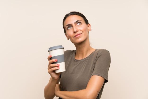 Jovem mulher segurando um café para viagem, olhando para cima enquanto sorrindo