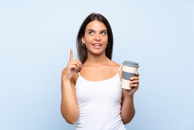Jovem mulher segurando um café para viagem sobre parede azul isolada, com a intenção de realizar a solução enquanto levanta um dedo