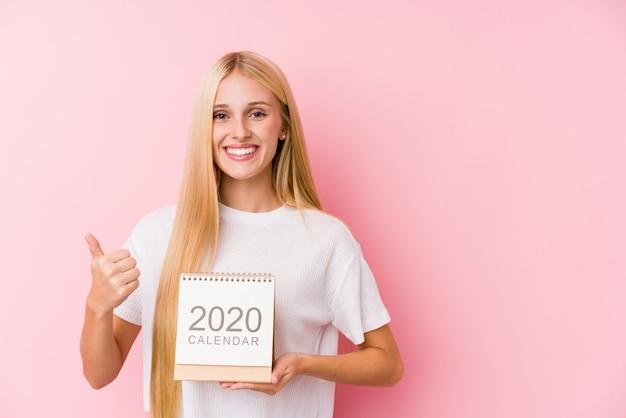 Jovem mulher segurando um calendário 2020 sorrindo e levantando o polegar