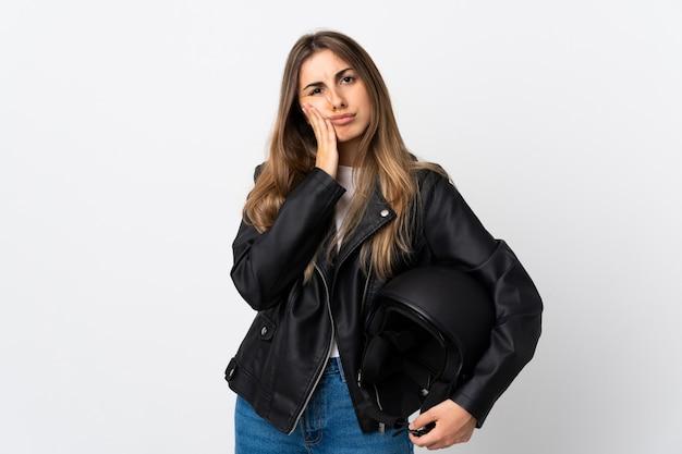 Jovem mulher segurando um capacete de moto isolado parede branca infeliz e frustrada