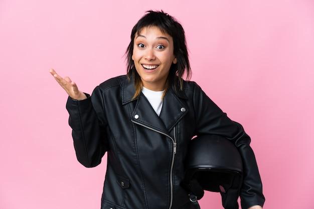 Jovem mulher segurando um capacete de moto parede rosa com expressão facial de surpresa