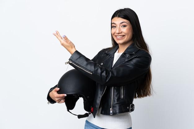 Jovem mulher segurando um capacete de moto sobre branco isolado, estendendo as mãos para o lado para convidar para vir