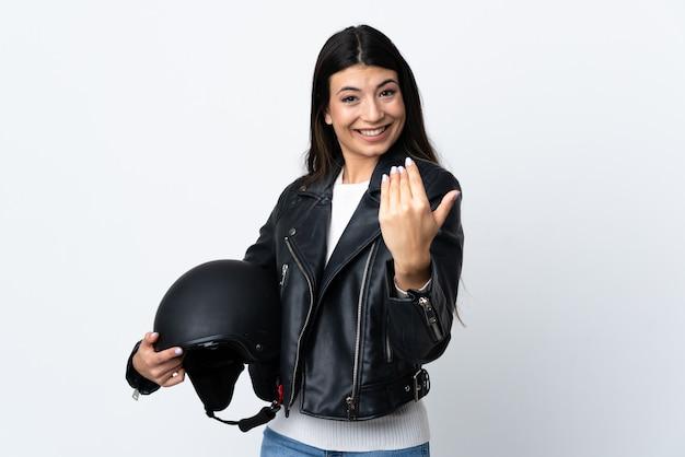 Jovem mulher segurando um capacete de moto sobre parede branca isolada, convidando para vir