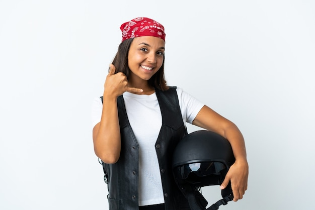 Jovem mulher segurando um capacete de motocicleta isolado no branco, fazendo gesto de telefone. ligue-me de volta sinal