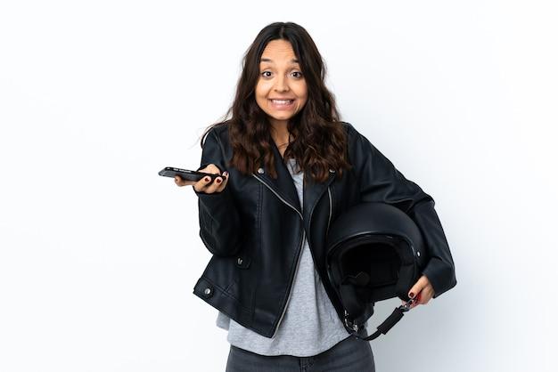 Jovem mulher segurando um capacete de motocicleta sobre um fundo branco isolado, conversando com alguém ao telefone celular